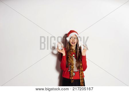happy young girl in a red Christmas sweater holding a Christmas tree toys,round neck gold tinsel