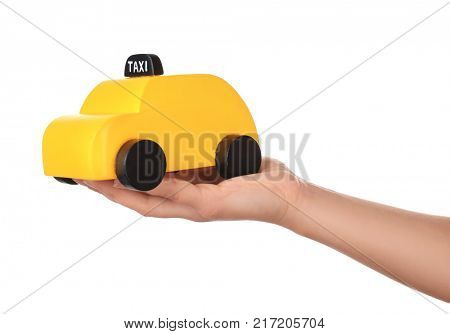 Woman holding yellow toy taxi cab on white background