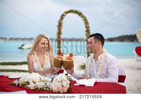 Groom and bride drink coconut cocktails at wedding table with lei of flowers on the beach of tropical island on Maldives. Turquoise ocean and ceremony arch on background.
