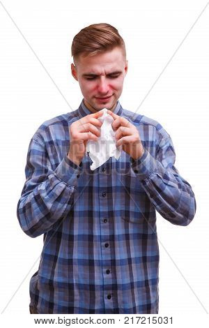 Sick guy with a stuffy nose in a blue shirt wants to wipe his nose with a napkin on a white isolated background