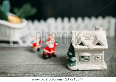 Black background. A white picket fence. Toy Santa Claus