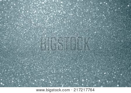 Silver glitter and sparkling blur bokeh light effect on snow white background. Glittering silver or shining particles texture with sparkling light for modern Christmas background design template
