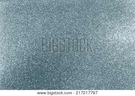 Silver glitter texture background with blur light effect and shiny sparkling particles. Glittering silver or shining snow light for modern trendy festive Christmas background design template