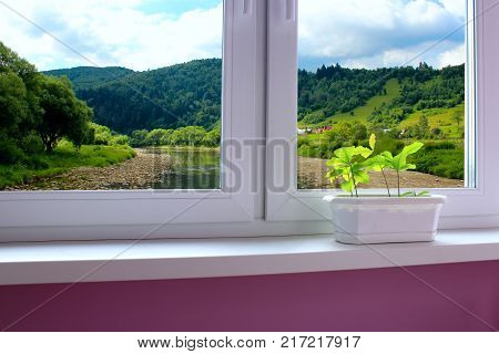 cozy room with window overlooking the beautiful summer mountain landscape