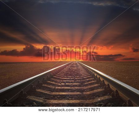 red sunset with rails going away. rails going away into the dark landscape with fiery red sunset