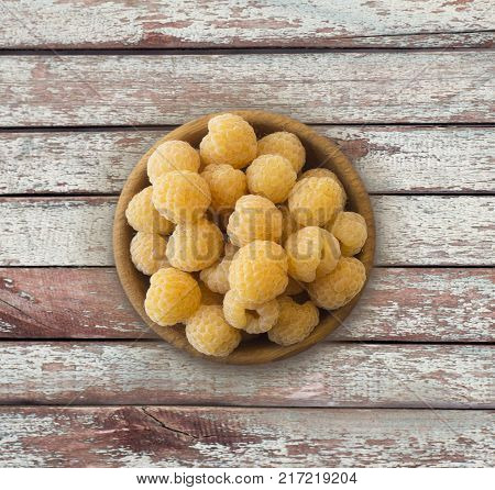 Raspberry top view. Sweet yellow raspberries on a wooden background. Raspberry in a wooden bowl with copy space for text.