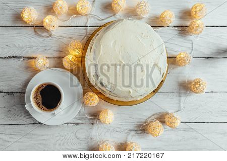 Celebration Homemade Biscuit Cake With White Cream On A White Wooden Table. Twinkling Lights Around