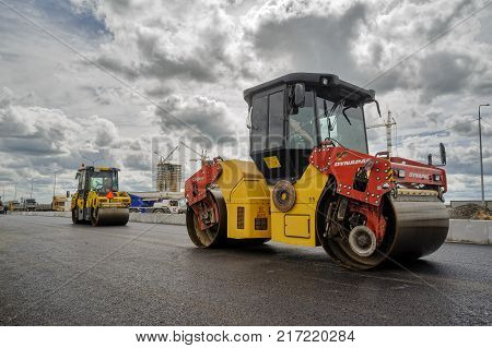 Tyumen, Russia - June 1, 2017: JSC Mostostroy-11. Construction of two-level outcome on bypass road on Fedyuninskogo and Permyakova streets intersection. Road rollers compressing asphalt to highway construction