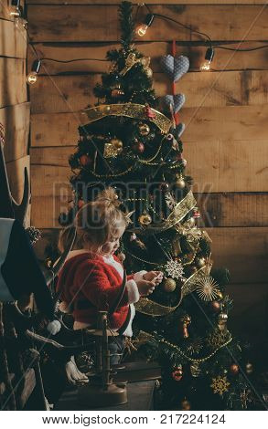 Santa claus kid at Christmas tree. Christmas happy child read wish letter. New year small boy with paper. Winter holiday and vacation. Xmas party celebration.