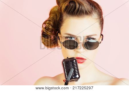 Woman singer with stylish retro hair and makeup. Pin up young girl on pink background radio. Music look and retro style pinup. Beauty and vintage fashion. Girl in glasses sing in microphone.