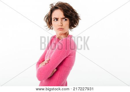 Portrait of an upset angry girl standing and looking away at copy space isolated over white background