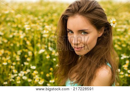 Photo of pretty brunette woman in chamomile field, cute female enjoying smell of daisy, sweet girl with closed eyes relaxed on flowers meadow, spring nature, having fun outdoor