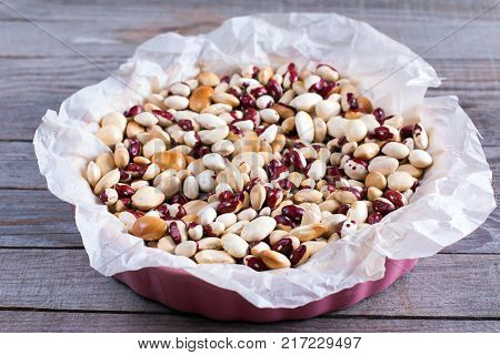 ceramic beans in an unbaked pie case lined with baking parchment