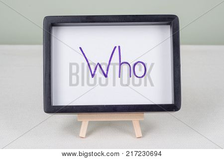 Text word WHO, in black frame, on white table.