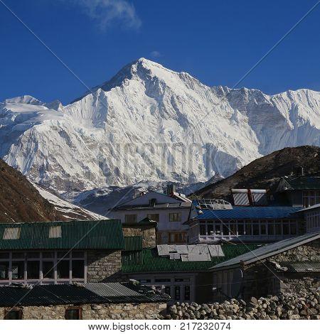 Lodges in Gokyo and snow covered mount Cho Oyu. Spring scene in Solu Khumbu Nepal.