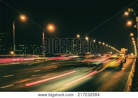 Abstract blurred light trails on motorway highway at dusk, image of urban speed traffic night. Urban modern background. Auto, city street lights and speed. Selective focus