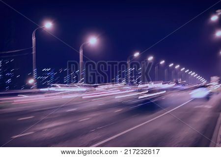 Abstract blurred light trails on motorway highway at dusk, image of urban speed traffic night. Toned urban modern background. Auto, city street lights and speed. Selective focus