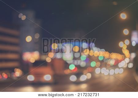 Urban street night traffic with bokeh lights, auto with brake lights, city street lights and speed. Toned abstract blurred background. Selective focus