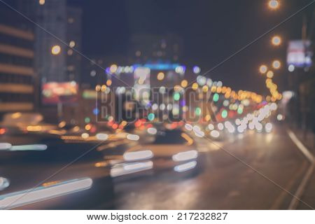 Urban street night traffic with bokeh lights. Blurred auto with brake lights, city street lights and speed. Abstract toned blur background
