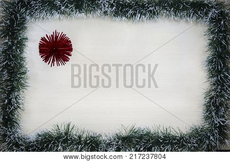 Christmas design-Christmas card fringed with pine needles and red balloons with place for text. Studio photography.