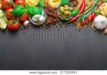 Traditional Italian food on a dark background with copy space, ingredients for cooking. Tomatoes on branch, olives, mozzarella, basil, rosemary, pepper, pasta. Top view, horizontal image