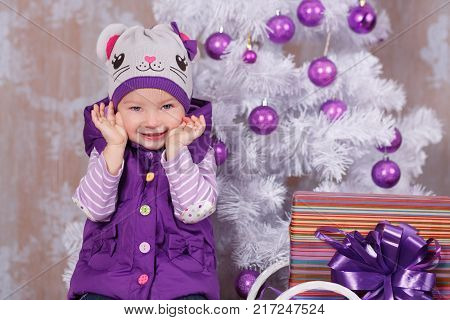 Christmas beautiful cute baby girl posing in casual clothes close to new year pine green tree with presents pillows and toy horse in studio scene.