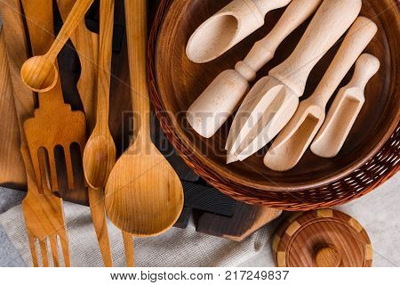 On the table are various wooden kitchen utensils, utensils, boards and a wicker basket. View from above. Close up.