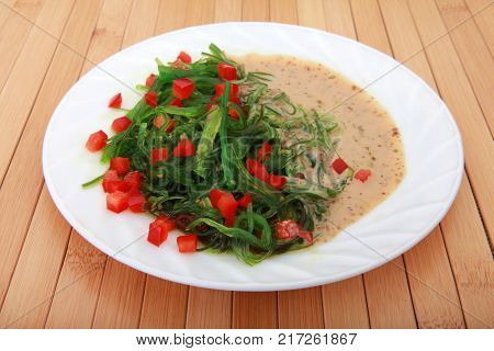 Chinese traditional fresh salad Chukka with spicy warm sauce and sweet red pepper on white plate studio quality menu poster for elite restaurant or caffe sport bar