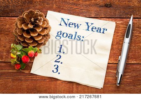 New Years goals list on napkin against rustic barn wood