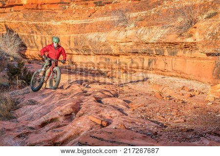 riding a fat mountain bike on a slickrock at the sandstone canyon bottom - Ruby Wash in Red Mountain Open Space north of Fort Collins, Colorado