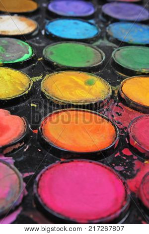 Watercolor used paint palette. Used palette can illustrate creative art work or any other concept. Colorful artsy background wallpaper.