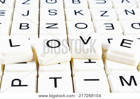 Love title text word crossword. Alphabet letter blocks game texture background. White alphabetical letters on black background. White educational toy block with words on board table. Words.