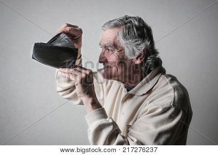 Elderly man looking into his empty wallet