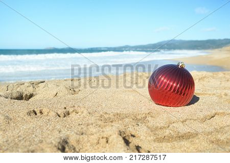 Christmas at the beach, red ball ornament in the sand on sunny day. Display, copy space