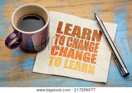 Learn to change, change to learn -  word abstract on a napkin with a cup of espresso coffee