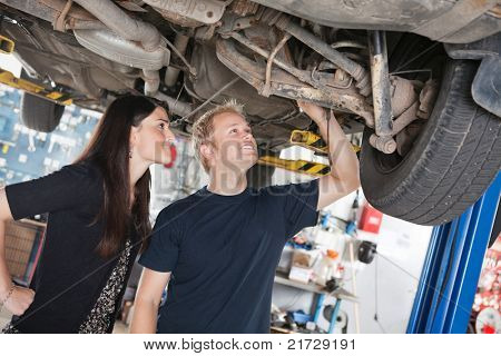Young mechanic and woman looking at machine of car in auto repair shop