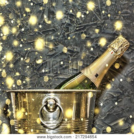 Champagne in a bucket for ice against a stone wall. Golden snowflakes, falling snow. Concept: Christmas, New Year. top veiw