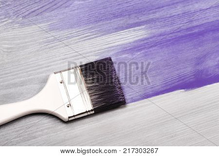 Painting white wooden surface with white paintbrush and Ultra Violet color color.