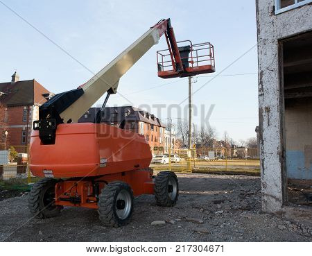 Boom Lift parked on Construction Site with boom raised