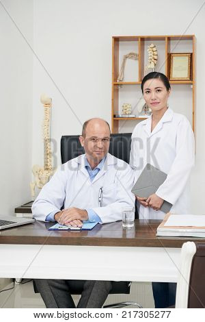 Professional osteopath and his assistant in office