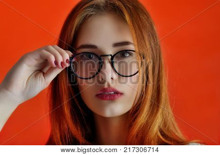 Portrait Of A Cheerful Caucasian Girl In Glasses On The Red Backgroung