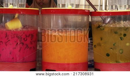 A woman selling tropical exotic and seasonal fruit juices on the street market in Kuala Lumpur Malaysia