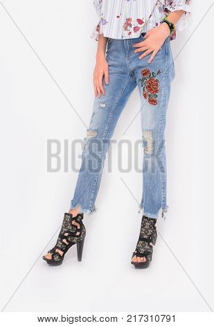 Woman legs in embroidered flowers jeans and leather shoes posing