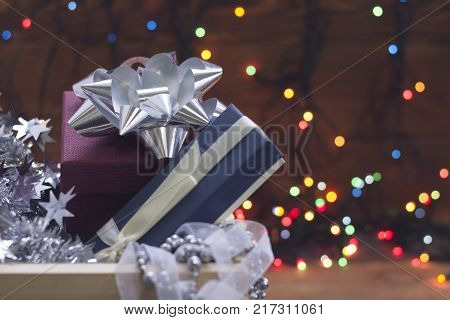 A purple gift box with a solver bow, blue gift box with a white ribbon and a silver garland in a wooden drawer. Colored fairy lights at the back. Dark blurred bokeh.