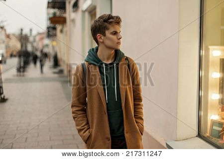 Stylish Young Man With Hair In A Fashionable Coat With Hoodie And Black Bag Sitting On A Street In T