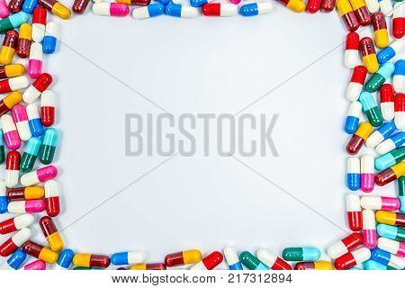 Colorful of antibiotics capsule pills rectangle frame on white background with copy space. Drug resistance concept. Antibiotics drug use with reasonable and global healthcare concept.