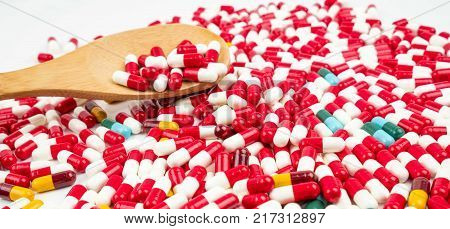 Colorful of antibiotic capsules pills and wood spoon on white background. Drug resistance concept. Antibiotics drug use with reasonable and global healthcare concept.