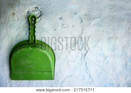 Green Colored Dustpan Hanging On The Wall.concept Of Cleanliness And Neatness.