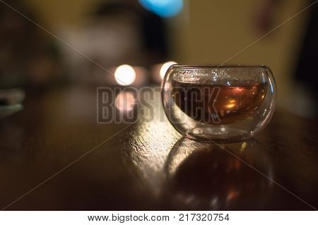 Transparent small glass of Chinese black tea on a table shot contre-jour to candlelight