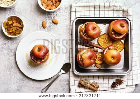 Stuffed apples with granola cinnamon nuts and honey on stone background. Healthy fruit dessert. Top view flat lay food